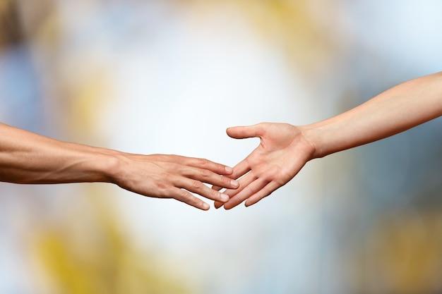 Руки протягиваются и касаются друг друга на фоне боке