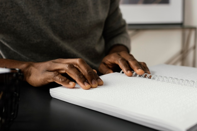Hands reading braille notebook close up