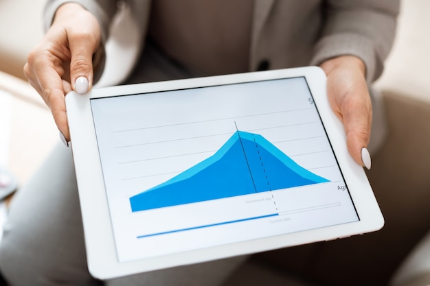 Hands of real estate agent holding digital tablet with blue financial graph on display while making presentation to client