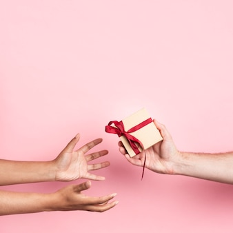 Hands receiving a small wrapped gift with ribbon