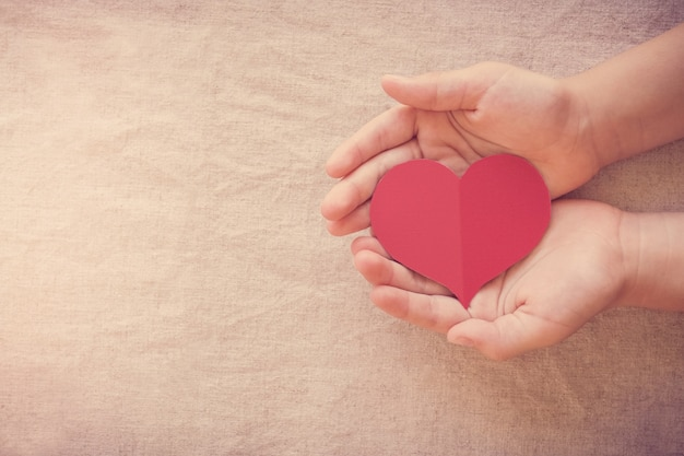 Hands and red heart, health insurance, donation and charity concept, world heart day