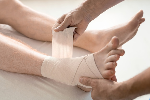 Hands of rehabilitation clinician wrapping foot and ankle of patient with flexible bandage during medical procedure on couch in hospital