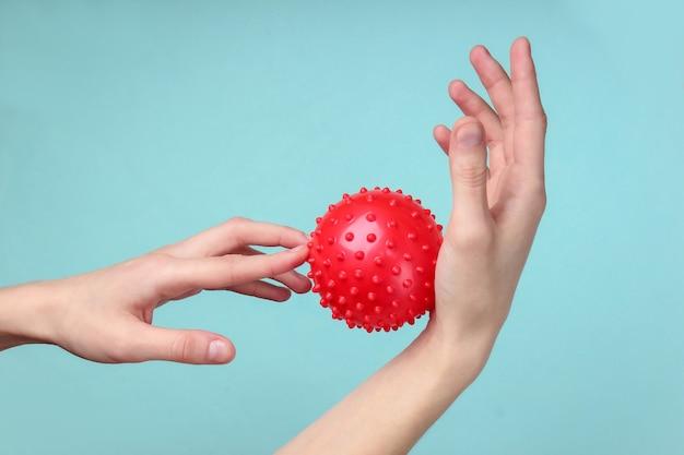 青に赤いマッサージボールで手をリラックスさせます。抗ストレス玩具