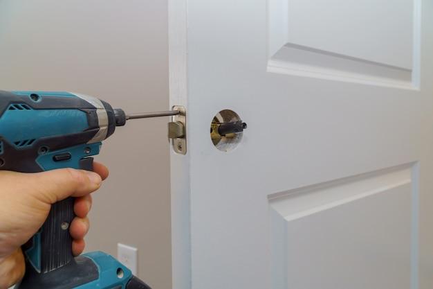 Hands repairing a door lock with a screwdriver