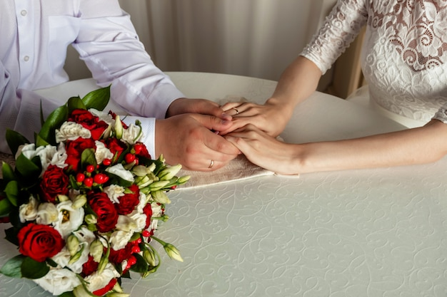 Hands and rings of just married couple with wedding bouquet.