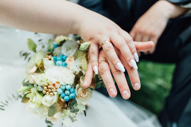 Hands and rings on wedding bouquet close up