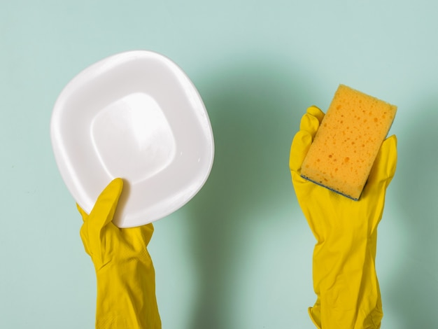 Hands in rubber gloves hold a foam sponge and a clean white plate. homework. washing dishes by hand.