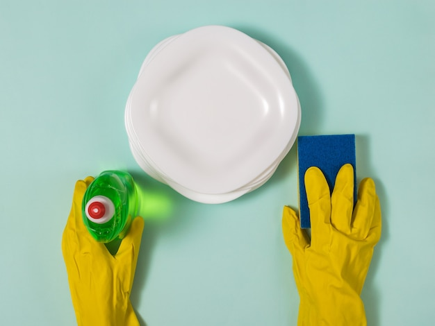 Hands in rubber gloves hold a sponge and gel against clean plates. homework. washing dishes by hand.
