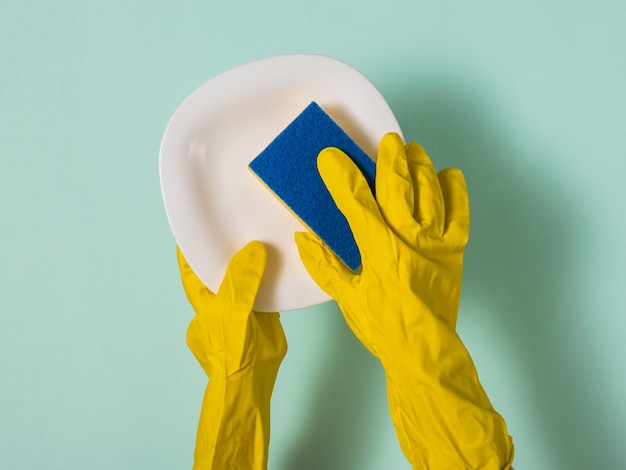 Hands in rubber gloves wash white dishes on a blue surface