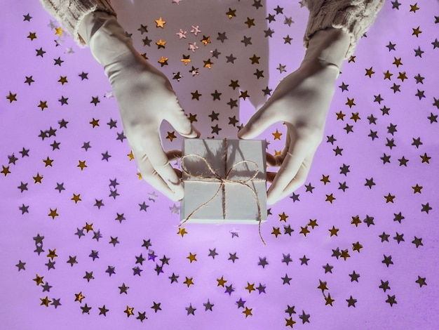 Hands in rubber protective gloves hold a white gift box golden and silver confetti stars
