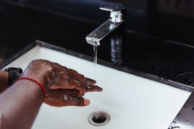 Hands rubbing with soap and water in sinks