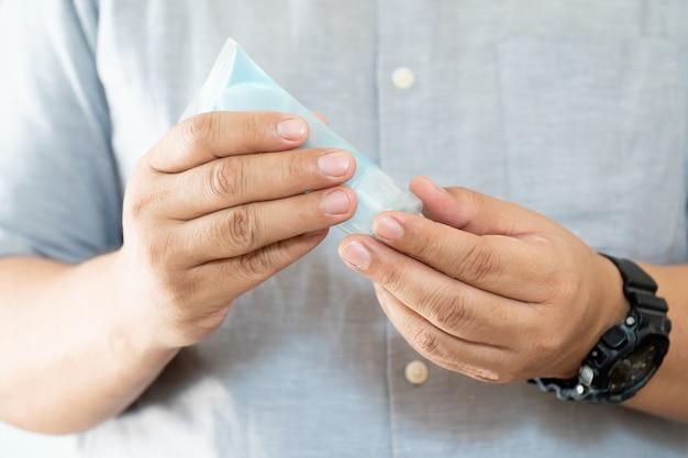 手消毒剤アルコールゲル。男は手を掃除するために使用し、コロナウイルス、covid-19から保護します。