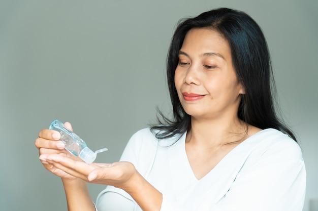 손 소독제 알코올 젤. 여성은 손을 씻고 코로나 바이러스, covid-19로부터 보호합니다.