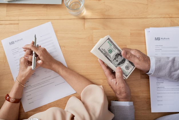 Hands of senior couple filling sale deed form and paying with cash for new house