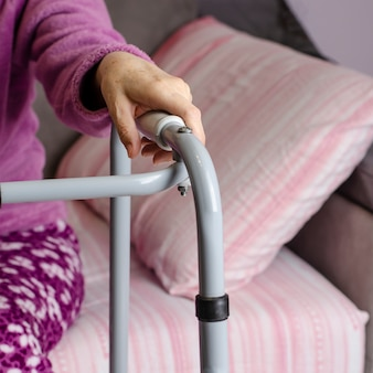 Hands of a senior woman on the handles of a walker.