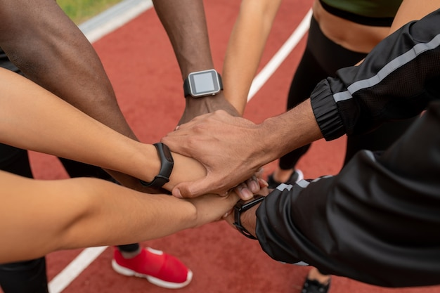 Hands of several young multicultural male and female athletes making pile over stadium racetrack