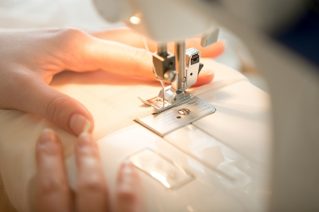 Hands at sewing machine Free Photo