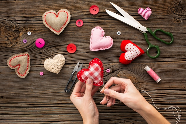 Hands sewing a red heart shape on wooden background