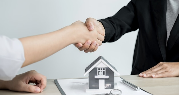 Hands shaking after real estate agents explain a business contract.
