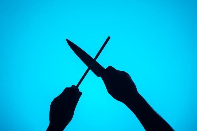 研ぎ棒でナイフを研ぐ手。料理の要素