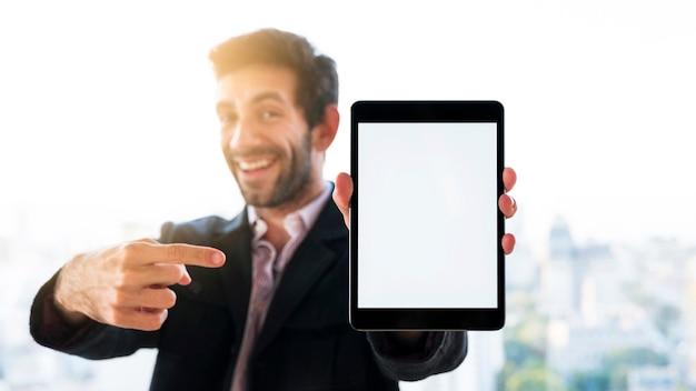 空白の画面を持つタブレットを示す手