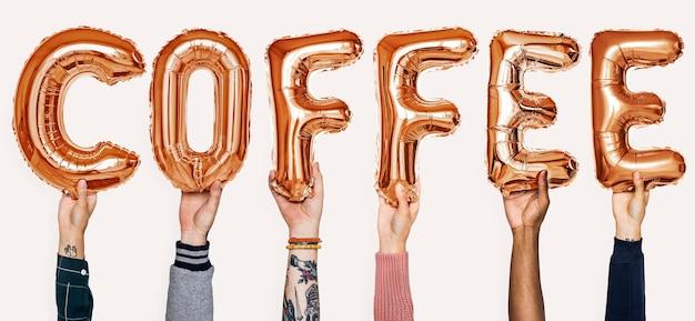 Mani che mostrano la parola di palloncini di caffè