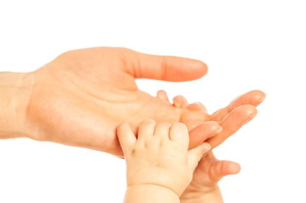 Hands of a small newborn baby hold on to the fingers of her mother s hands on a white