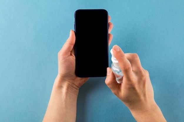 電話で消毒剤をスプレーする手