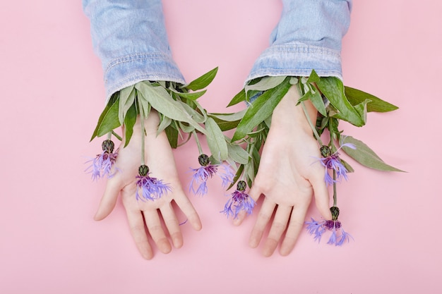 Hands and spring flowers are on a pink table skincare. nature cosmetics