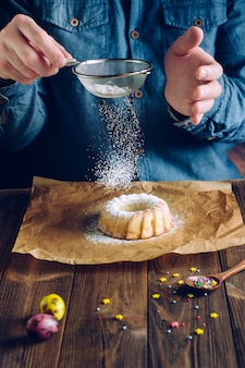 Hands sprinkling easter ring cake with icing sugar