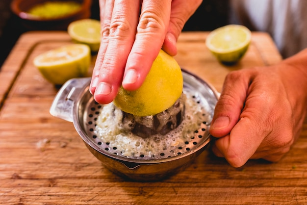 Hands squeezing the juice of a lemon.