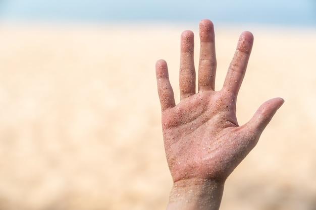 砂、ビーチ、海の背景で汚れた手。