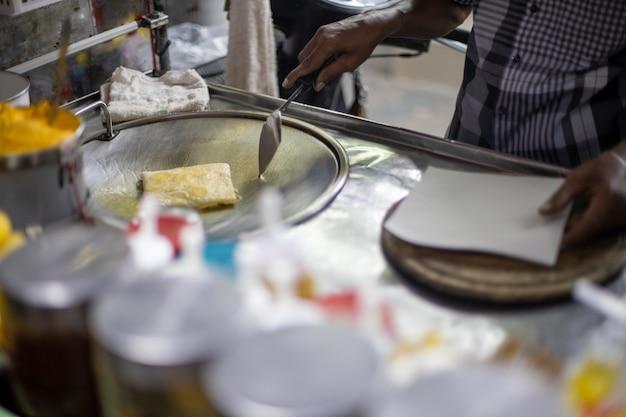 Hands of street vendor cooking thai style sweet roti bread on steel roti pan or big flat frying pan. enjoy thailand's street food.