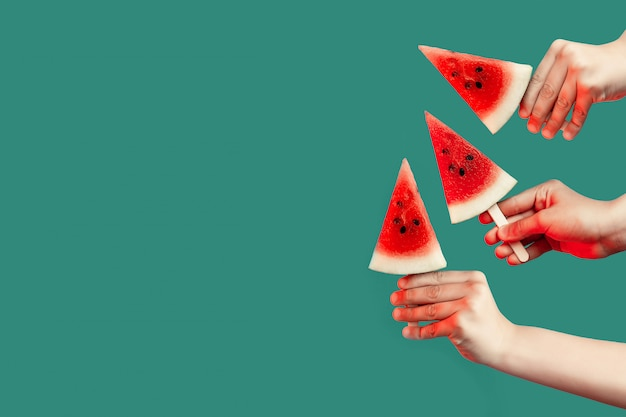 Hands stretch out pieces of watermelon on a stick