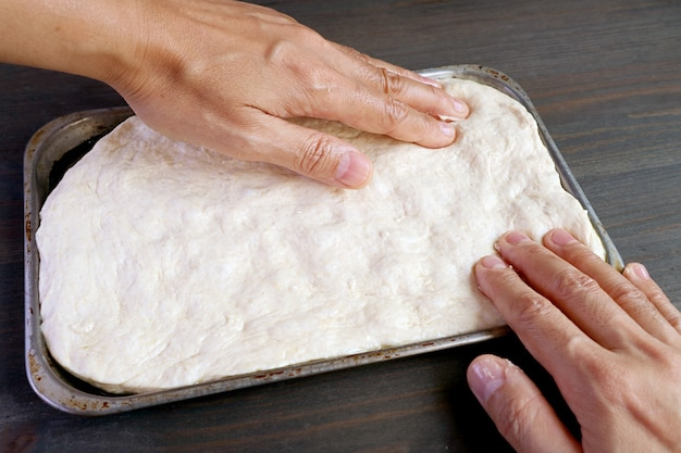 Hands stretching risen dough in a pan for baking pizza or bread