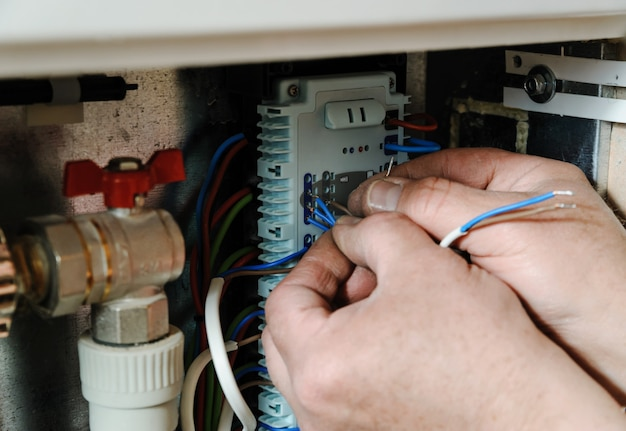 Hands switching signal wires in the home's heating system control.
