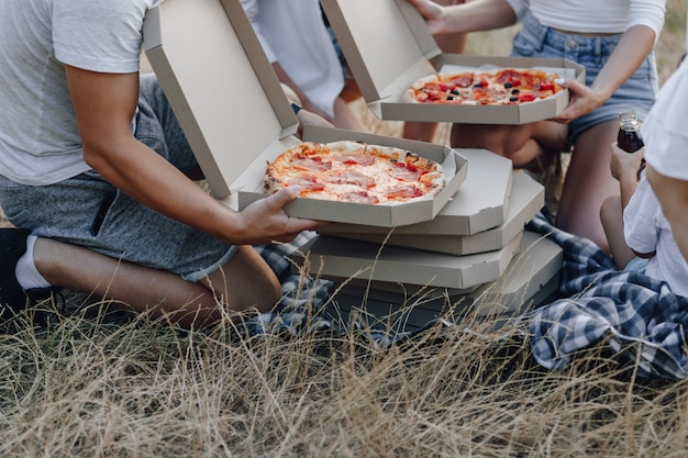Hands take out pizza from boxes at picnic