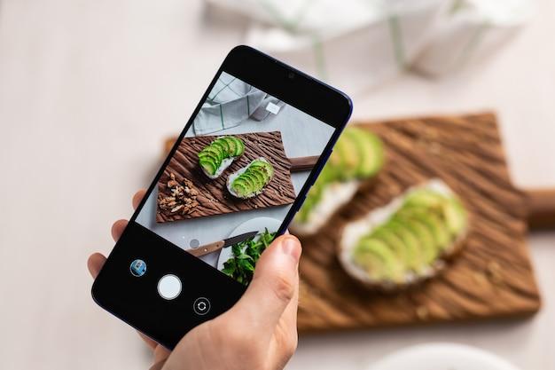 手は、テーブルの上に横たわっている2つの美しい健康的なサワークリームとアボカドサンドイッチのスマートフォンで写真を撮ります。ソーシャルメディアと食品のコンセプト