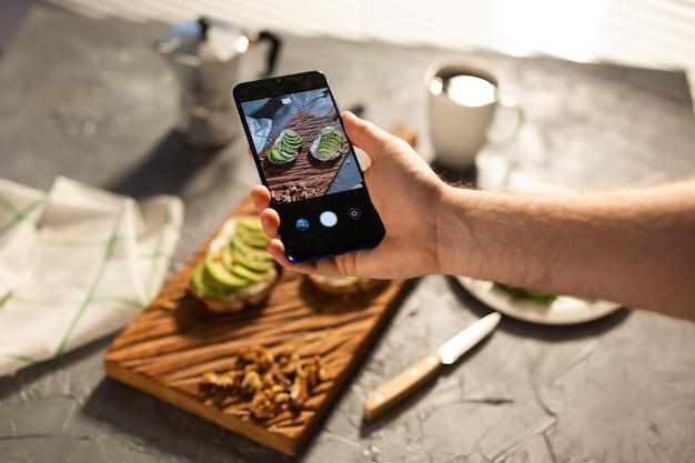 手は2つの美しい健康的なサワークリームと横たわっているアボカドサンドイッチのスマートフォンで写真を撮ります