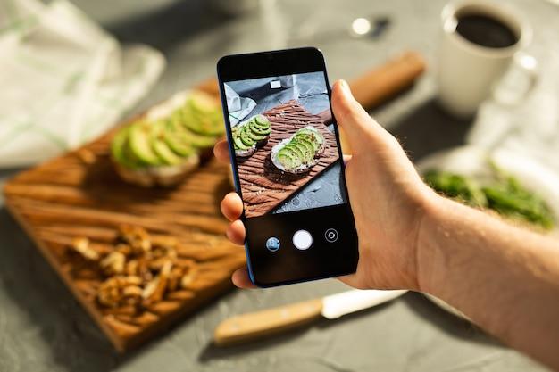 Руки фотографируют на смартфоне лежат два красивых здоровых бутерброда со сметаной и авокадо