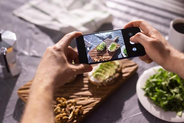 手は2つの美しい健康的なサワークリームとアボカドサンドイッチのスマートフォンで写真を撮ります