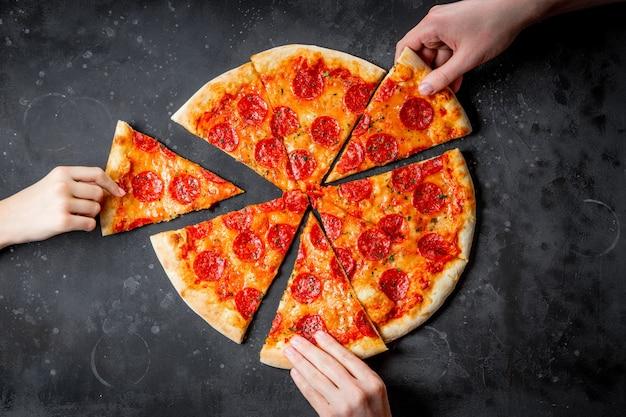 손은 검은 배경, 평면도에 고전적인 이탈리아 피자 페퍼로니 조각을 가져갑니다. 고품질 사진