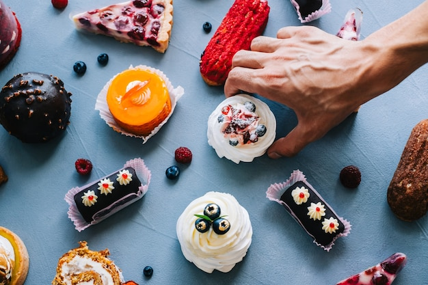 많은 다른 디저트와 함께 테이블에서 케이크를 가져가는 손.
