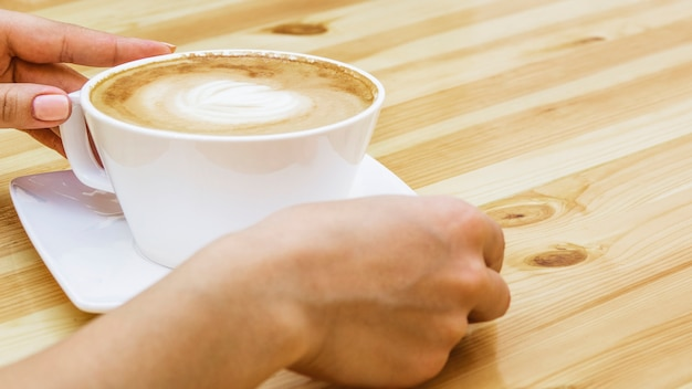 Hands taking cup of coffee