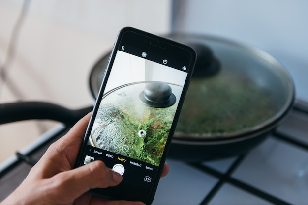 Hands taking photo of pan with greens with smartphone