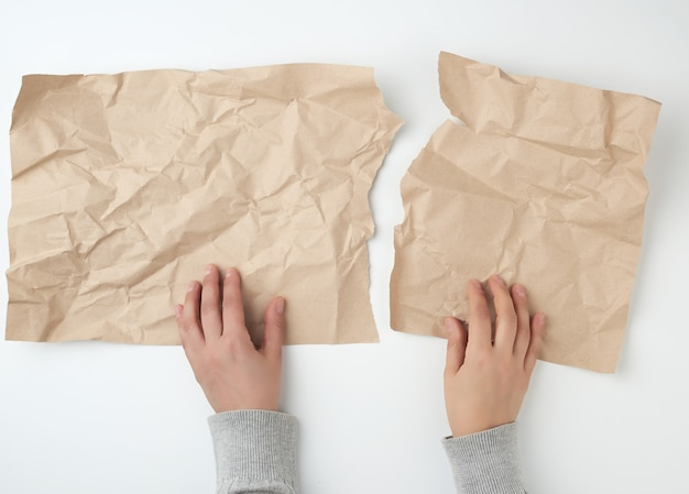 Hands tearing a sheet of brown craft paper