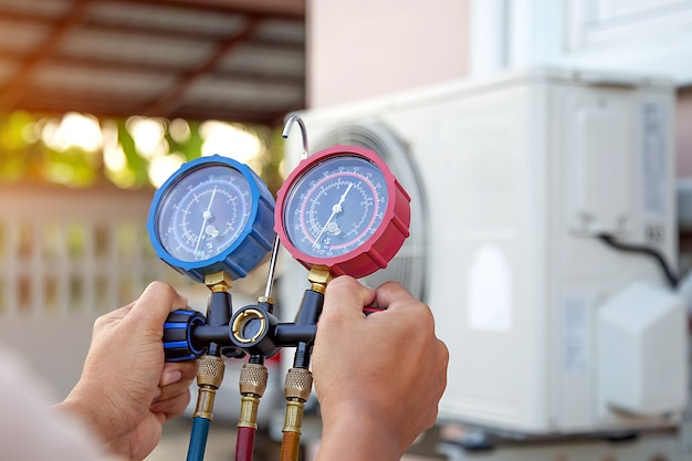 Hands of technician are using a measuring tool to check vacuum pump evacuates air for air conditioner.