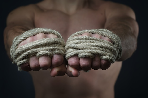 Hands thai boxer in the foreground, the traditional hemp rope wrapped to match or training