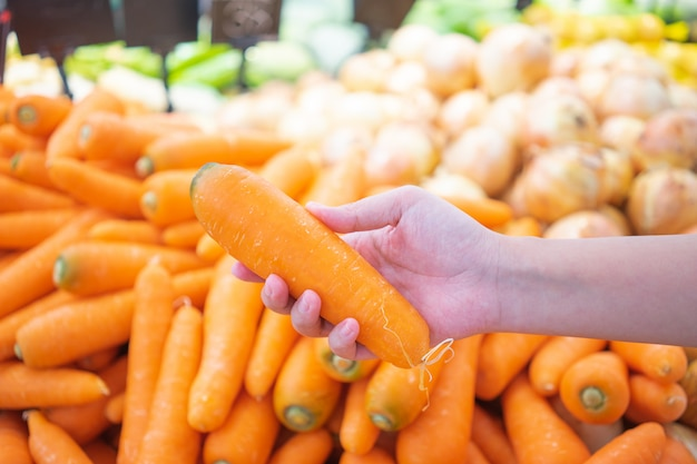 Hands that are picking fruits and vegetables from the shelf to select quality products.