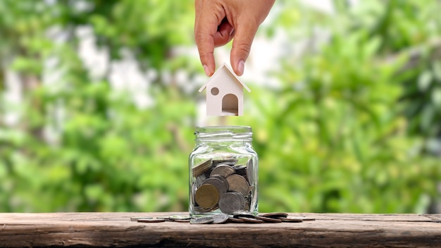 Руки, которые модели домов кладут в банку для сбережений, идеи экономии денег, чтобы купить дом.